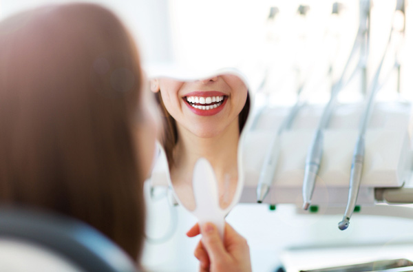 Woman looking at her smile in a mirror at Riverstone Family Dentistry in Vancouver, WA